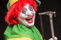 Enge kwade clown met een lelijke glimlach en zaag op een zwarte backgroun Stock Afbeeldingen