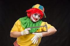 Enge kwade clown met een lelijke glimlach en zaag op een zwarte backgroun Royalty-vrije Stock Foto