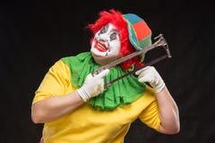 Enge kwade clown met een lelijke glimlach en zaag op een zwarte backgroun Stock Afbeelding