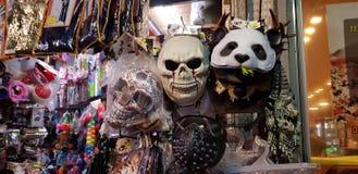 Enge maskers en ander plastic kleurrijk die materiaal voor kinderen voor verkoop in een winkel vóór Joodse purimmaskerade worden  stock foto's