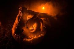 Enge oranje pompoen met gesneden ogen en een glimlach met het branden van kaarsen en een bijl op een donkere achtergrond met bran Royalty-vrije Stock Afbeelding