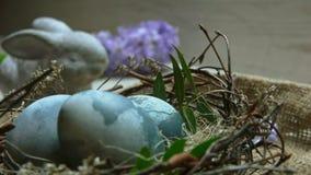 Enge Osterei in der Nähe von Hibiskus-gefärbt im Nest auf dem Hintergrund von Blumen stock footage