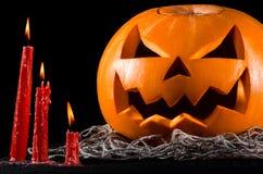 Enge pompoen, hefboomlantaarn, pompoen Halloween, rode kaarsen op een zwarte achtergrond, Halloween-thema, pompoenmoordenaar Royalty-vrije Stock Foto