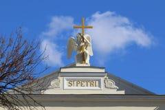 Engel, der ein Kreuz auf einem Hintergrund des blauen Himmels mit Wolken umarmt Lizenzfreie Stockbilder