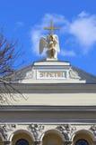 Engel, der ein Kreuz auf einem Hintergrund des blauen Himmels mit Wolken an umarmt Lizenzfreies Stockfoto