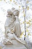 Engel hinter Frauenstatue Stockfotos