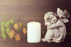 Engel, kaars en bloemen stock afbeelding