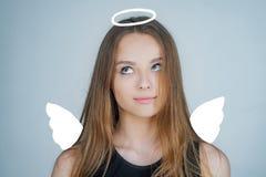 Engel Kind met engelachtig karakter De mooie en leuke jeugd Meisjesengel met halo in witte engelenkleding Rood nam toe stock foto