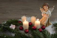 Engel met het branden van kaarsen in de sneeuw en de rode Kerstmisballen Stock Foto
