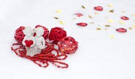 Engel mit Herzen auf weißem Schnee Stockfotos