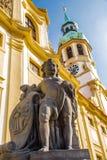 Engel mit Schild gegen Prag Loretta und blauer Himmel lizenzfreie stockfotografie