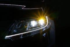 Engel mustert glühende Optiklinse des Xenonscheinwerfers stockfoto