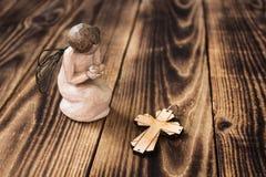 Engel und Christkreuz auf hölzernem Hintergrund Stockfoto