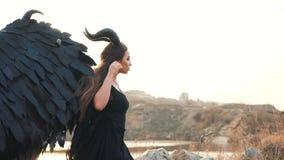 Engel van dood en oorlog, meisje in zwarte lange uitstekende kleding met kantkokers alleen naast groot meer, dame met sterk stock videobeelden