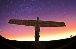 Engel van het noorden bij nacht met sterslepen Stock Fotografie