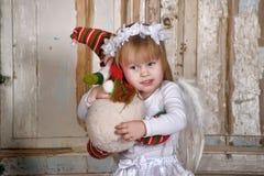 Engelachtig meisje met stuk speelgoed stock fotografie