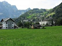 Engelberg town and Benedictine monastery, Switzerland. View of the picturesque town of Engelberg across a meadow backed by mountains, with its Benedictine stock photos