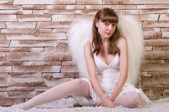 Engelenmeisje met baksteenachtergrond Stock Foto's