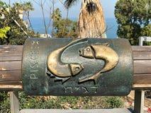 Engels en Hebreeuws metaalpisces astrologisch teken bij het Wensen van Brug in Oude Stad van Yaffa Israel stock afbeelding