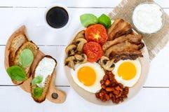 Engels ontbijt: eieren, bacon, bonen in tomatensaus, paddestoelen, tomaten, toost met roomkaas Stock Fotografie