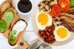 Engels ontbijt: eieren, bacon, bonen in tomatensaus, paddestoelen, tomaten, toost met roomkaas en een kop van koffie Stock Foto's