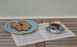 Engels theekopje met schotel en een cakeplaat met koekjes, het fijne porselein van beenchina, op een blad van muziek stock afbeelding