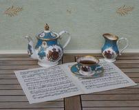 Engels theekopje met schotel, theepot en roomkruik, het fijne porselein van beenchina, op een blad van muziek stock foto
