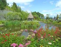 Engelse de stijltuin van het land met een feeplattelandshuisje op de vijver stock fotografie