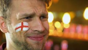 Engelse die voetbalventilator met vlag op wang over favoriete team verliezende gelijke wordt verstoord stock video