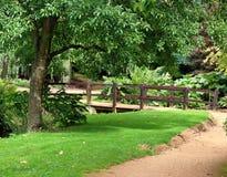 Engelse gemodelleerde tuin met voetgangersbrug over een stroom royalty-vrije stock foto's