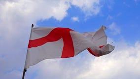 Engelse vlag tegen blauwe hemel in langzame motie stock videobeelden