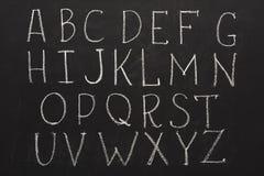 Engelsk abc som är skriftlig vid krita på svart tavla Fotografering för Bildbyråer