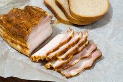 Engelsk bacon skivade delvist på Kraft papper arkivfoto