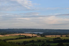 Engelsk bygd med sjön och fält Arkivbilder