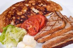Engelsk frukost med förvanskade ägg, tomater Arkivbild