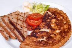 Engelsk frukost med förvanskade ägg, tomater Royaltyfria Bilder