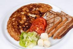 Engelsk frukost med förvanskade ägg, tomater Fotografering för Bildbyråer