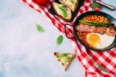 Engelsk frukostbegrepp med avokadorostat bröd över blå tappningbakgrund arkivfoton