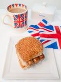 Engelsk korvsmörgåswithcup av te och flaggan Arkivbild