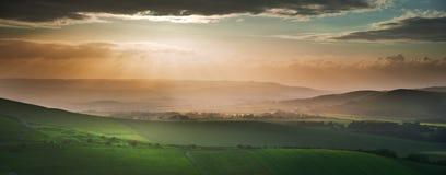 engelsk liggande för bygd över sommarsolnedgång arkivbild