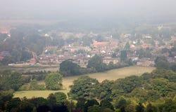 engelsk mistmorgon över säsongsbetonad town Arkivfoton