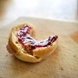 Engelsk muffin för frukost, med söt röd driftstopp- eller geléspridning överst och att sitta på den wood kornskärbrädan royaltyfri fotografi