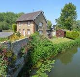 Engelsk stuga med den färgglade stugaträdgården och vägg på bankerna av floden Ouse Arkivfoton