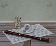 Engelsk tekopp och tefat med den blom- dekor- och silverkanten, metronom för musik och en kvarterflöjt på ett ark av musik royaltyfri fotografi