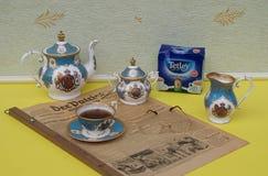 Engelsk teservis, en packe av original- engelska Tetleys teabags och läsningexponeringsglas på en gammal tysk dagstidningDer patr fotografering för bildbyråer
