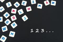 Engelska kulöra fyrkantbokstäver spridde på svart bakgrund med nummer 123 Royaltyfria Bilder