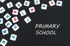 Engelska kulöra fyrkantbokstäver spridde på svart bakgrund med textgrundskola för barn mellan 5 och 11 år royaltyfri foto