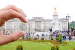 Engelska myntar att föreställa drottningen framme av Buckingham Palace Royaltyfri Foto
