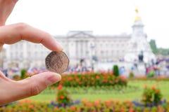 Engelska myntar att föreställa drottningen framme av Buckingham Palace Arkivfoto