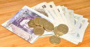 Engelska sedlar och mynt Arkivfoto